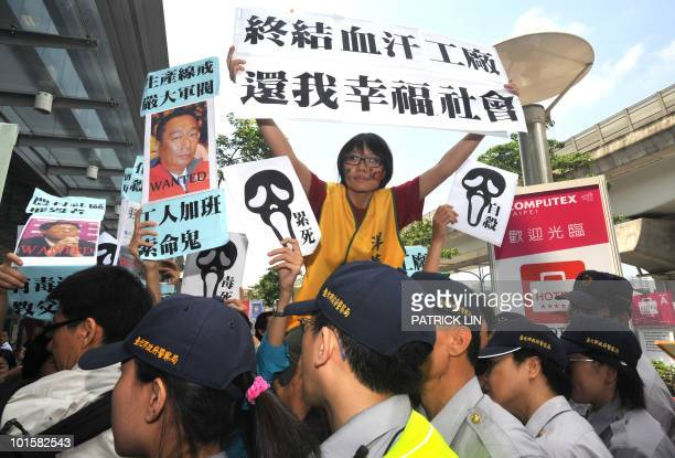 A woman demonstrator unfurls a protest sign reading 'Put an end to blood and sweat factories return to a happy society' while a portrait of Terry Gou...
