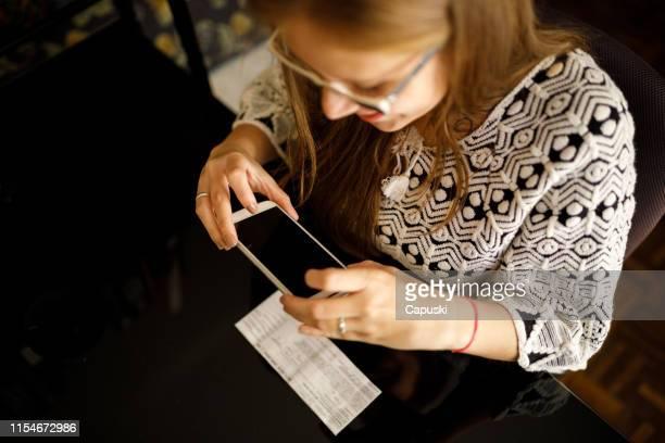 frau hinterlegt scheck per telefon - einzahlungsbeleg stock-fotos und bilder