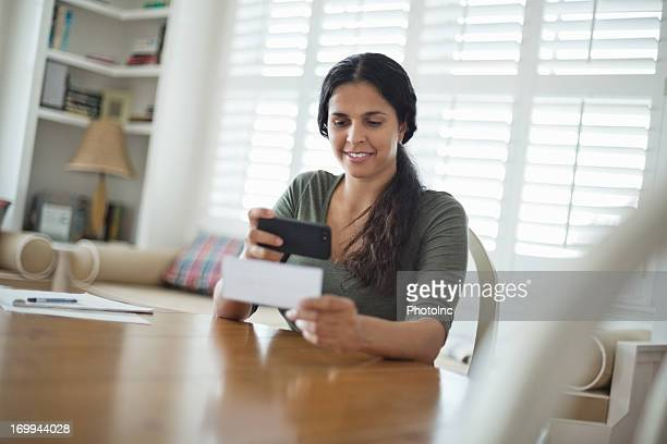 Woman Depositing Check Through Smart Phone At Table