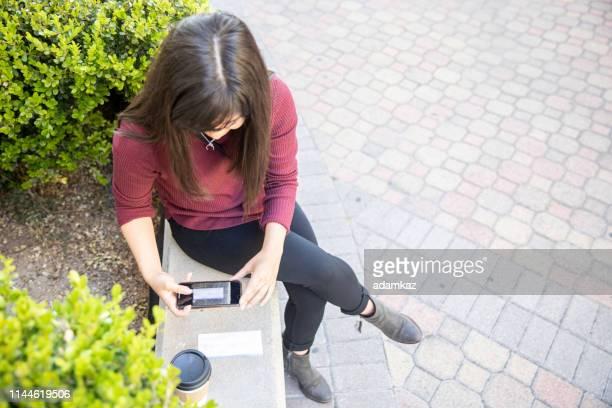 frau legt kontrollen mit smartphone hinterziehen - einzahlungsbeleg stock-fotos und bilder