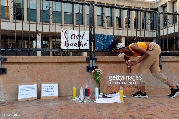 A woman deposits a candle in the John F Kennedy Plaza outside the Lowell Police Station during a peaceful vigil for George Floyd and other victims of...