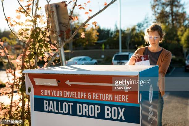 woman deposits absentee mail-in voters ballot - ballot box stock pictures, royalty-free photos & images