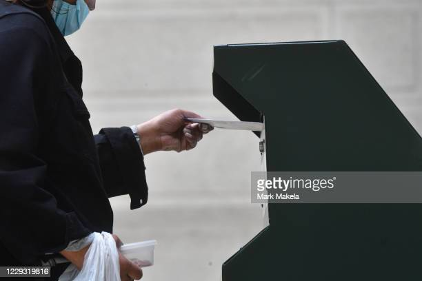 Woman deposits her ballot in an official ballot drop box at the satellite polling station outside Philadelphia City Hall on October 27, 2020 in...