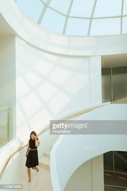 Woman descending staircase using mobile phone