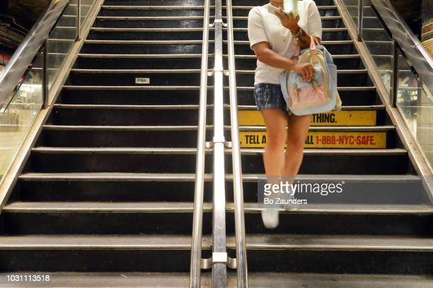 Woman descending stairs to subway station in Midtown Manhattan
