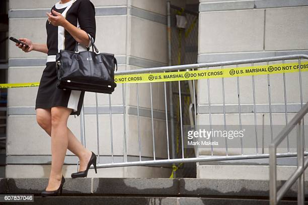 A woman descends stairs beside US Marshal security tape outside the Martin Luther King Jr Federal Courthouse during opening statements are heard in...