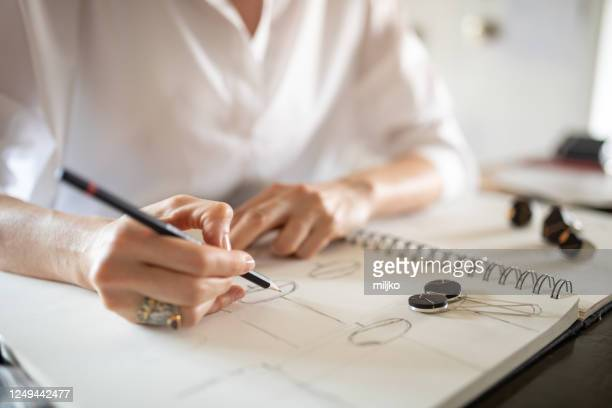woman designing jewelry in her atelier - jewellery stock pictures, royalty-free photos & images