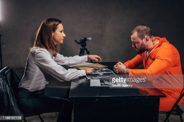 woman detective and prisoner sitting in interrogation room - confession law stock pictures, royalty-free photos & images