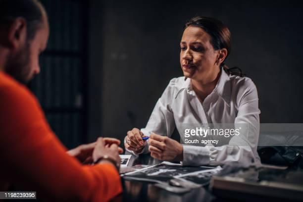 尋問室で男の囚人を尋問する女性刑事 - 執行猶予 ストックフォトと画像
