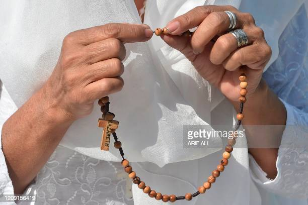 Woman devotee holds a rosary while she prays as she attends a Palm Sunday service outside the Sacred Heart Cathedral church during a...