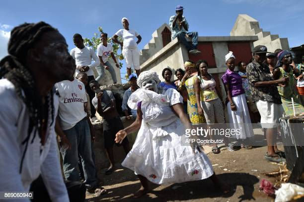 A woman devotee in the role of a spirit known as a Gede is seen during ceremonies honoring the Haitian voodoo spirit of Baron Samdi and Gede on the...