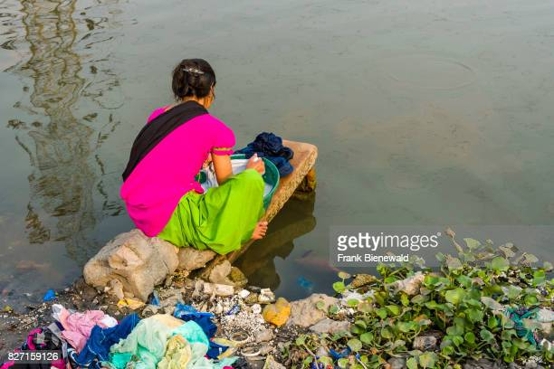 A woman dhobi is doing laundry at a lake in the suburb Topsia