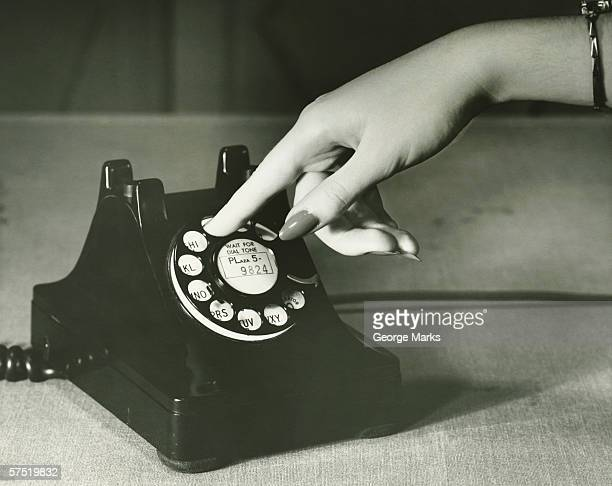 Woman dialing landline phone, close-up of hand, (B&W)