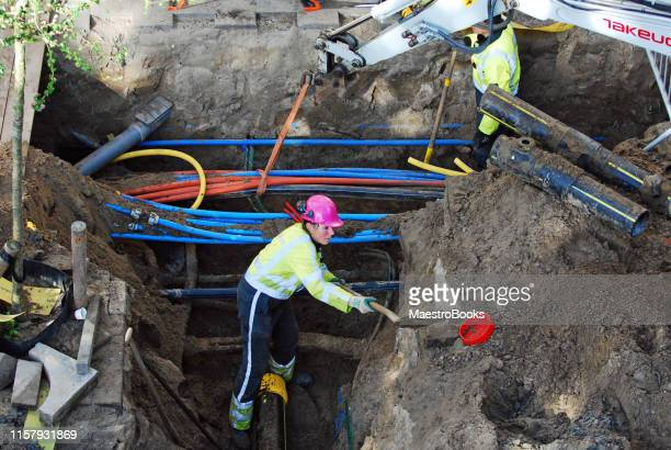 woman digging a sewer trench in the street. - trench stock pictures, royalty-free photos & images