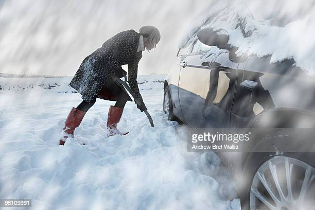 woman digging snow from back wheels of a car