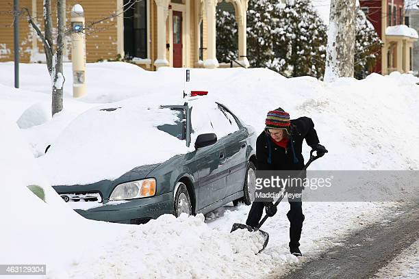 A woman digs her car out of a snow bank on February 10 2015 in Cambridge Massachusetts Boston was hit with its third major snow storm in three weeks...