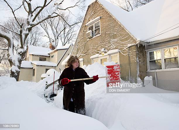 A woman digs out her sidewalk at her home January 27 2011 in the Bronx Borough of New York The overnight snow left more than a foot of snow in the...