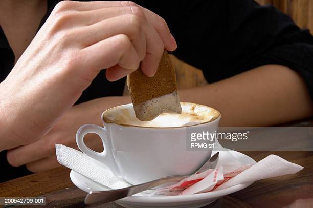 Woman dipping bisuit into coffee, close-up
