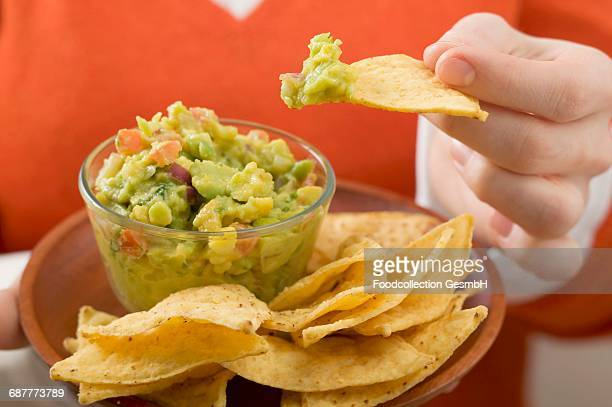 Woman dipping nacho in guacamole
