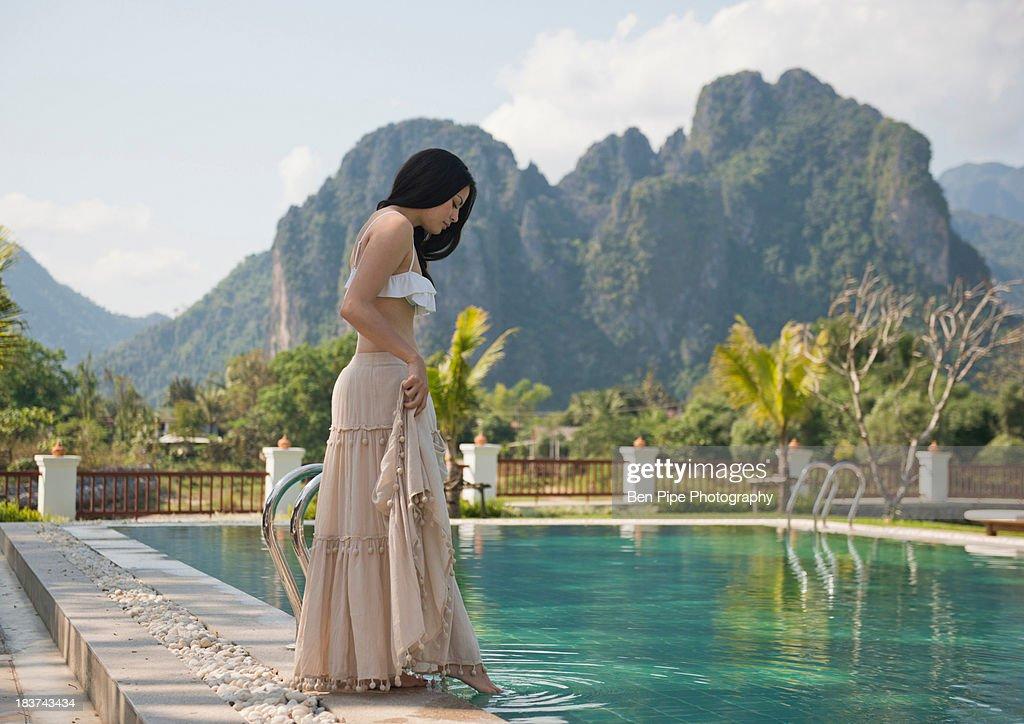 Woman dipping toe in swimming pool, Vang Vieng, Laos : Stock Photo