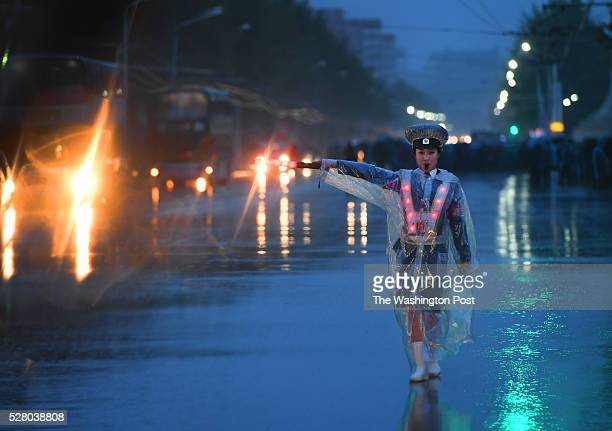 A woman directs traffic in the pouring rain in Pyongyang North Korea on May 3 2016 The city is preparing for the Workers' Party Congress starting on...