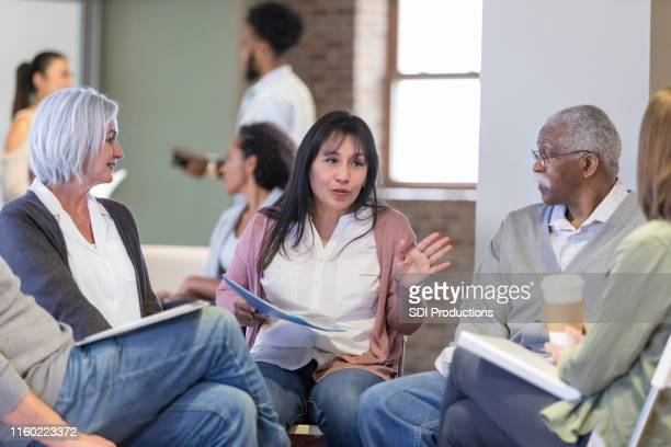 woman discusses neighborhood issues during hoa meeting - group therapy stock pictures, royalty-free photos & images