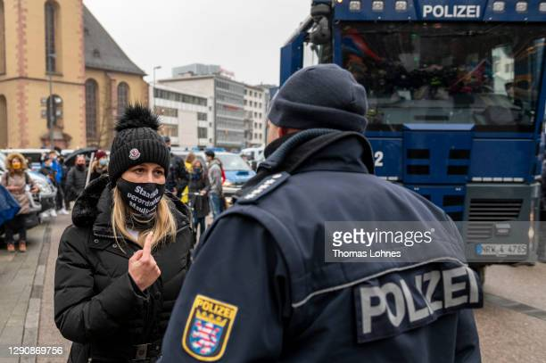 Woman discusses with a police officer in front of a water cannon while opponents of what they claim are restrictions to their personal freedoms due...