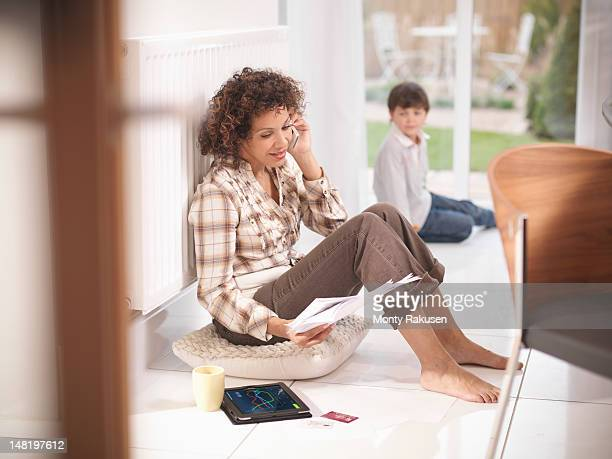 Woman discussing energy bills on telephone in energy efficient house
