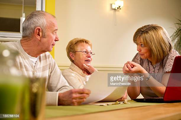 A woman discussing paperwork at a table with an older couple