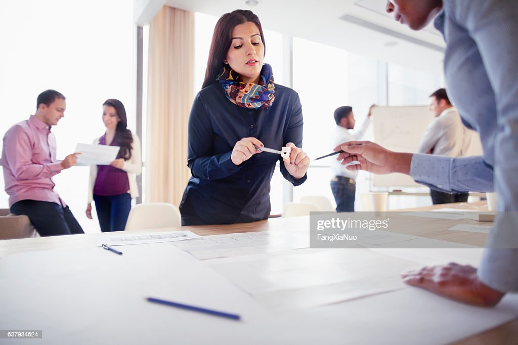 Woman discussing part design with colleague in innovation studio : Stock Photo