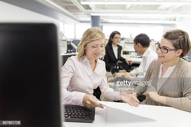 Woman discussing plans with colleague in office
