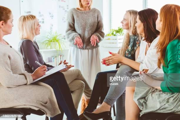 mujer discutiendo con grupo durante sesión de terapia - izusek fotografías e imágenes de stock