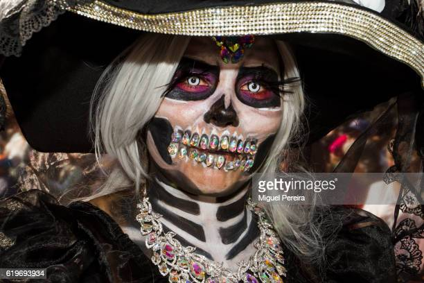 Woman disguised as a 'Katrina' inspired by the drawings of Mexican artist Jose Guadalupe Posada stares at the crowd during the Day of the Dead...