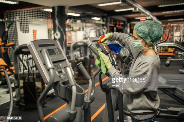 woman disinfecting and cleaning gym - miljko stock pictures, royalty-free photos & images