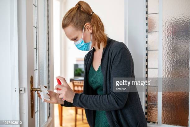 woman disinfecting door handle during covid-19 pandemic - rubbing alcohol stock pictures, royalty-free photos & images