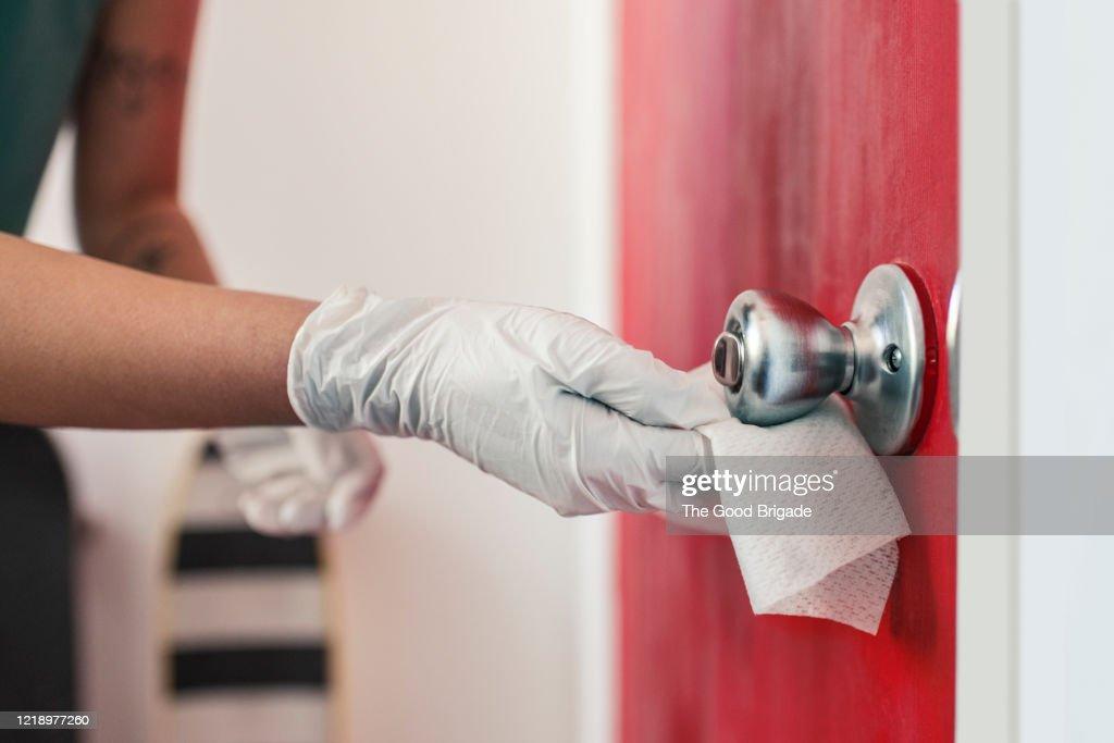 Woman disinfecting door handle : Stock Photo