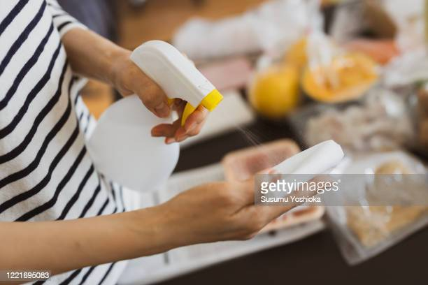 woman disinfecting food delivered to her home - cleaning product stock pictures, royalty-free photos & images