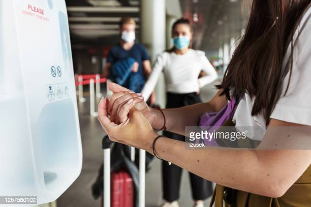 woman disinfecting hands at airport terminal - hand sanitiser stock pictures, royalty-free photos & images