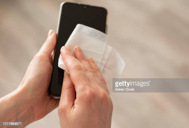woman disinfecting phone - cleaning agent stock pictures, royalty-free photos & images
