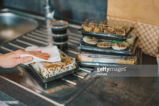 woman disinfecting takeaway sushi boxes - box container stock pictures, royalty-free photos & images