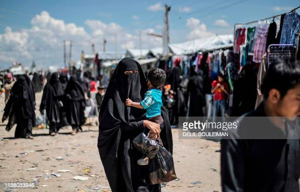 A woman displaced from Syria's eastern Deir Ezzor province carries child as she walks in alHol camp for displaced people in alHasakeh governorate in...