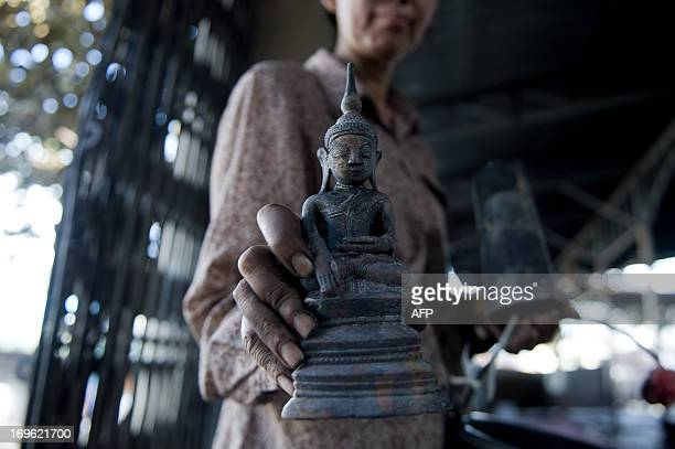 Woman displays a Buddha statue which she found in her demolished shop near the destroyed mosque in Lashio, Shan state of Myanmar on May 29, 2013....