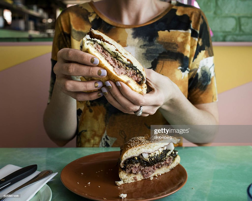 A woman displays a Green Chili Cheeseburger for a photograph at Mission Cantina restaurant in New York, U.S., on Tuesday, April 19, 2016. Top chefs pick their all-time favorites, from burgers with fat, mid-rare patties dripping with juice to thin, crisp disks of beef smothered with cheese. These are the ones the true masters crave when they're off duty. Photographer: Eric Medsker/Bloomberg via Getty Images