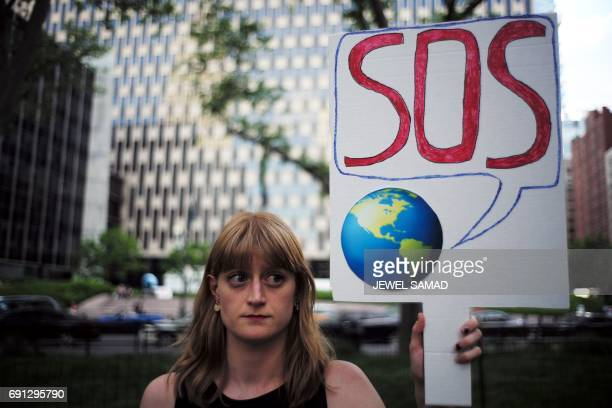 A woman displays a placard during a demonstration in New York on June 1 to protest US President Donald Trump's decision to pull out of the 195nation...
