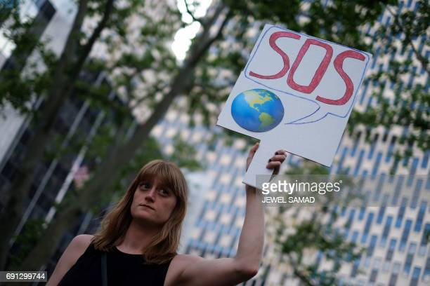 A woman displays a placard during a demonstrationo in New York on June 1 to protest US President Donald Trump's decision to pull out of the 195nation...