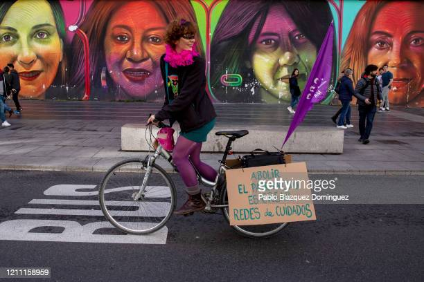 A woman displays a placard reading 'Abolishing patriarchy is creating care networks' as she takes part in a feminist bicycle protest during...