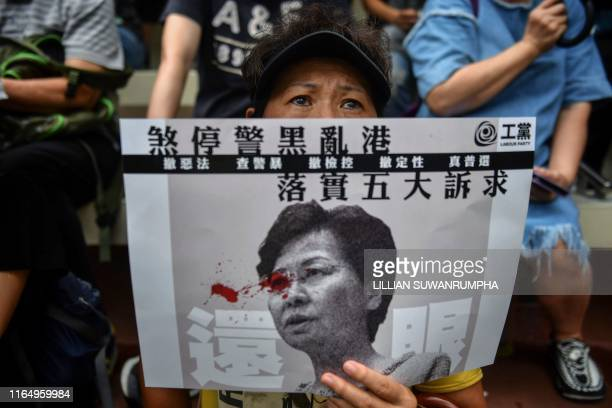 Woman displays a poster bearing an image of Hong Kong Chief Executive Carrie Lam during a protest at Southorn Playground in Hong Kong on August 31,...