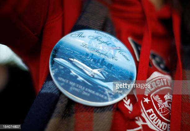A woman displays a souvenir badge as the Space Shuttle Endeavour is moved to the California Science Center on October 13 2012 in Inglewood California...