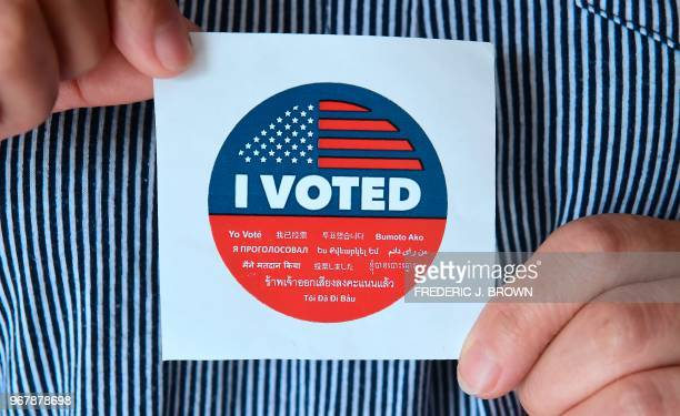 A woman displays a sticker given to voters outside a polling station in Los Angeles California on June 5 2018 as Californians go to the polls today...