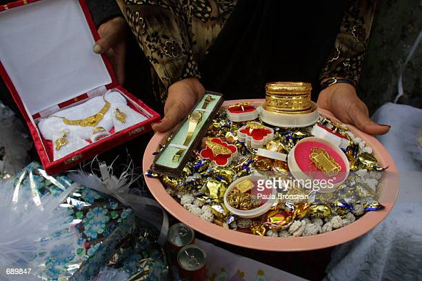 A woman displays gifts given by the bridetobe Najilla Ahmadis family for her engagement party January